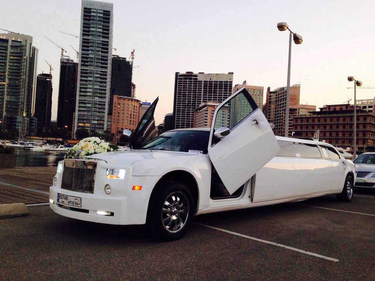White wedding limousine phantom car with bridal flowers decoration