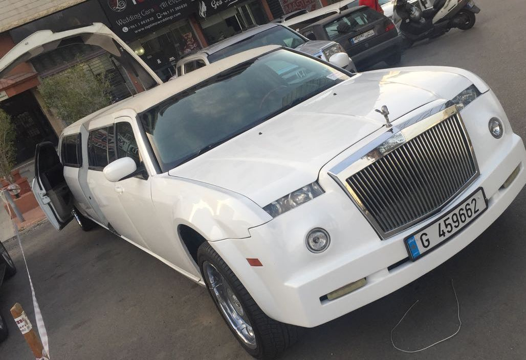 A White Phantom Limousine Parked under building with doors open and a Lebanese registration plate number